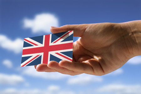 hand holding small flag of  Great Britain Imagens