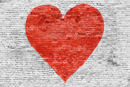 Symbol of love painted on white brick wall Imagens