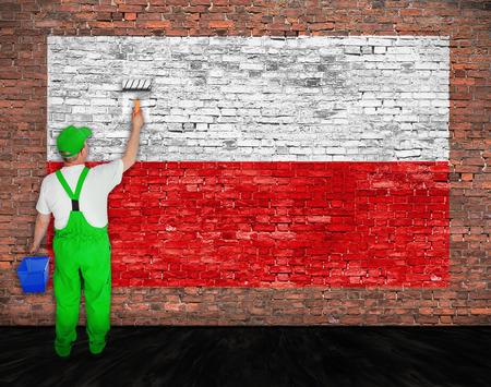 Huisschilder schildert vlag van Polen op oude bakstenen muur