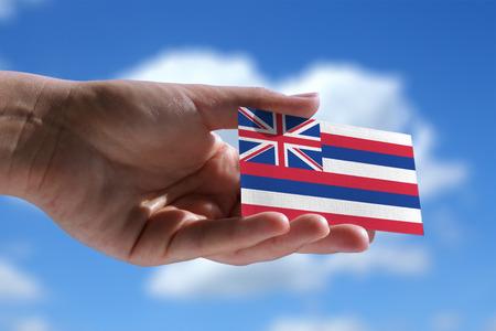 Kleine Hawaiiaanse vlag tegen hemel met cumuluswolken