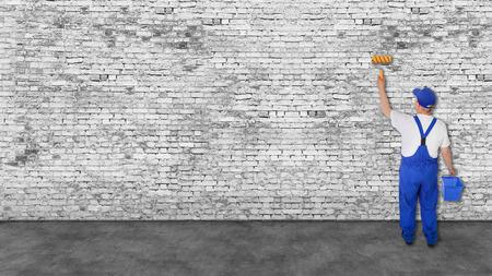 huisschilder dekt zeer lange witte bakstenen muur