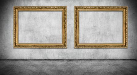 Twee oude gouden frames op grijze muur
