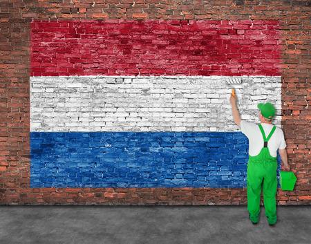Huisschilder schildert vlag van Hetherlands op oude bakstenen muur Stockfoto