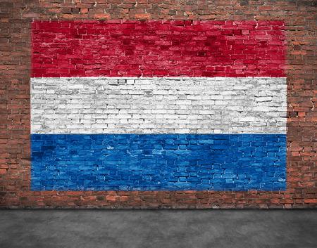 Vlag van Nederland geschilderd over oude bakstenen muur