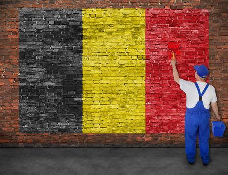 Huisschilder schildert vlag van België op oude bakstenen muur