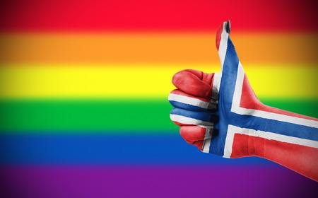 Concept foto - Positieve houding van Noorwegen voor de LGBT-gemeenschap. Hand tegen regenboogvlag. Focus ligt op de hand.