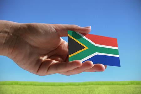 Kleine vlag van de Republiek van Zuid-Afrika tegen mooie landschap met gras