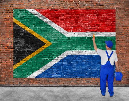 Huisschilder schildert vlag van de Republiek Zuid-Afrika op oude bakstenen muur