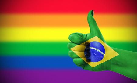 Concept foto - Positieve houding van Brazilië voor de LGBT-gemeenschap. Hand tegen regenboogvlag. Focus ligt op de hand. Stockfoto