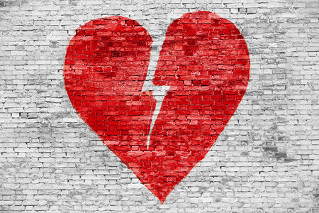 Shape of broken heart painted on white brick wall Stockfoto