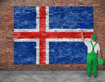 Schilder schildert vlag van IJsland op oude bakstenen muur, te bekijken van achter