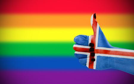 Concept foto - Positieve houding van IJsland voor de LGBT-gemeenschap. Hand tegen regenboogvlag. Focus ligt op de hand. Stockfoto