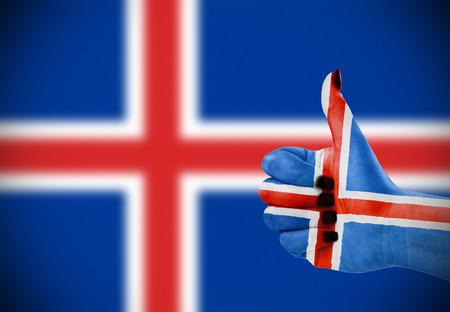 Vlag van IJsland op de vrouwelijke hand, tweede, defocused vlag op achtergrond. Stockfoto