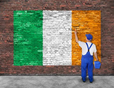 Huisschilder schildert vlag van Ierland op oude bakstenen muur, bekijken van achter Stockfoto
