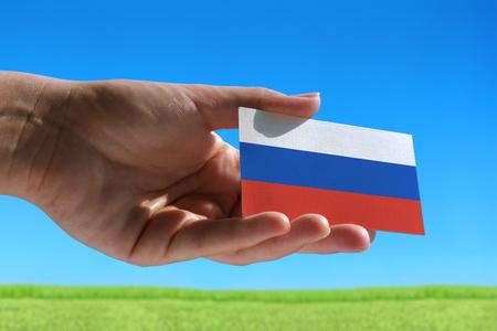 Kleine vlag van Rusland tegen mooie landschap met gras