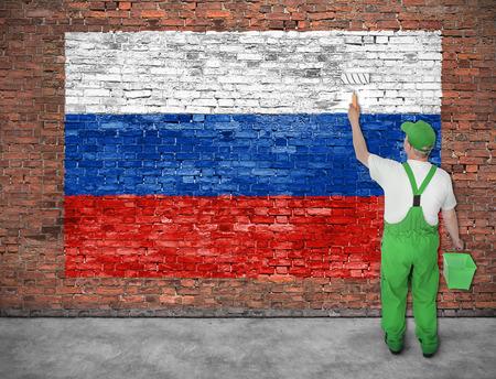 Huisschilder schildert de vlag van Rusland op oude bakstenen muur Stockfoto - 49446468