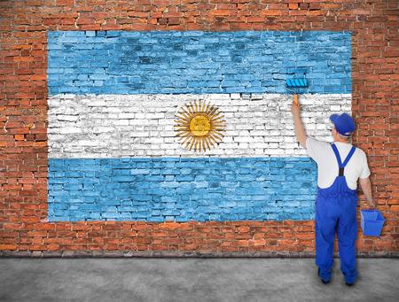 Huisschilder schildert vlag van Argentinië op oude bakstenen muur