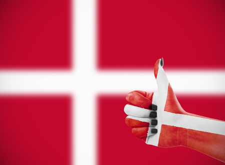 Vlag van Denemarken op de vrouwelijke hand, tweede, defocused vlag op achtergrond. Stockfoto - 50400953