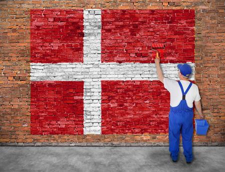 Huisschilder schildert vlag van Denemarken op oude bakstenen muur Stockfoto
