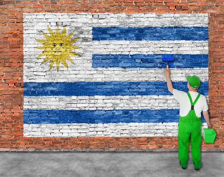 Huisschilder schildert vlag van Uruguay op oude bakstenen muur