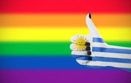 Concept foto - Positieve houding van Uruguay voor de LGBT-gemeenschap. Hand tegen regenboogvlag. Focus ligt op de hand. Stockfoto