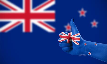 Vlag van Nieuw-Zeland op vrouwelijke hand, tweede, onscherpe vlag op achtergrond