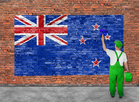 Huisschilder schildert de vlag van Nieuw-Zeland op oude bakstenen muur