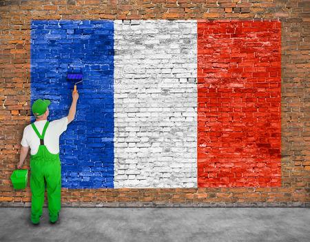 Huisschilder schildert de vlag van Frankrijk op oude bakstenen muur Stockfoto - 49790319