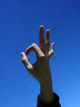 fingers showing the okay sign against the blue sky