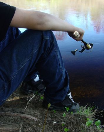 a boy sits fishing along a river bank