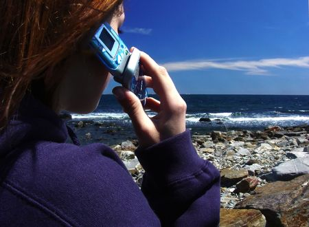 girl talking on the cell phone at the ocean photo