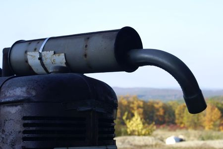 an antique rusty muffler on an old farm tractor photo