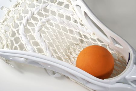 lax: a white lacrosse stick head and an orange ball