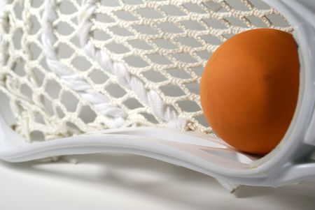 a white lacrosse stick head and an orange ball