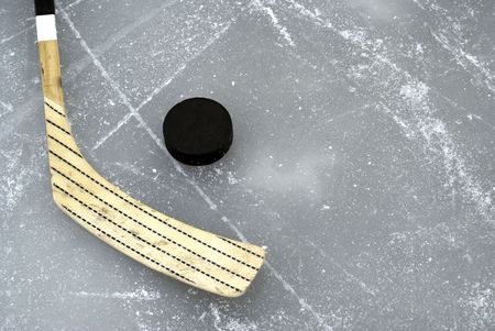 a hockey stick and puck on the ice photo
