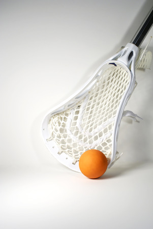 a white lacrosse stick head and an orange ball Stock Photo - 1478039