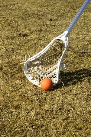 scooping: a white lacrosse stick scooping the ball off the ground