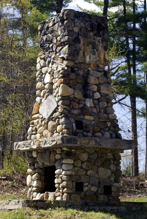 outdoor fireplace: a fire place constructed of stones by the lake Stock Photo