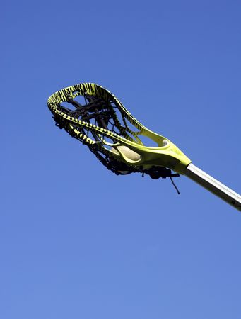 weave ball: a green striped lacrosse stick and ball against a blue sky Stock Photo