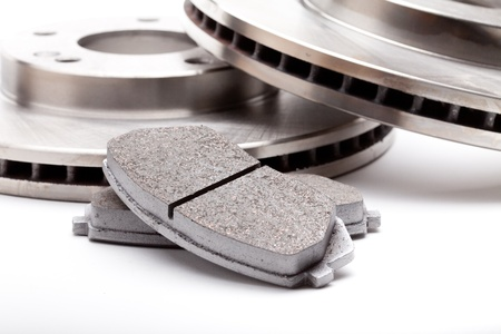 Closeup studio shot of two front brake disks and pads for a modern car on a white background with a light shadow Stock Photo