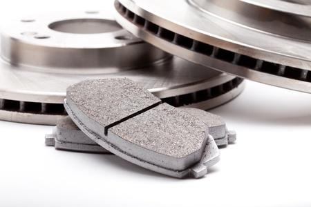 frenos: Primer disparo de estudio de dos discos delanteros de freno y pastillas para un coche moderno en un fondo blanco con una sombra de la luz