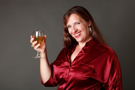 white wine: Woman in red satin blouse holding a glass of white wine smiling