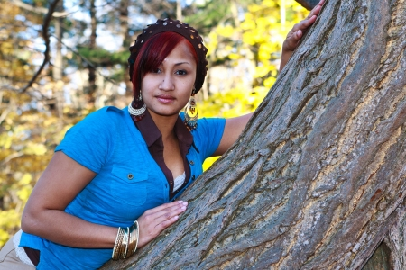location shot: Location shot of a beautiful and trendy Hispanic woman leaning on a tree in a park Stock Photo