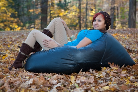 location shot: Location shot of a beautiful and trendy Hispanic woman sitting on a bean bag in the middle of a leaf covered field Stock Photo