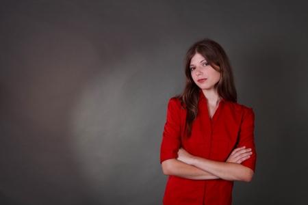 mani incrociate: Studio shot di una Tean in forma e assetto bruna in una camicia rossa e pantaloncini su uno sfondo grigio Archivio Fotografico