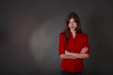 Studio shot of a fit and trim brunette tean in a red shirt and shorts on a grey background photo