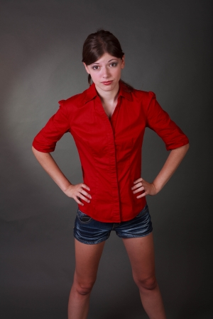 hands on hips: Studio shot of a fit and trim brunette tean in a red shirt and shorts on a grey background with angry hands out Stock Photo