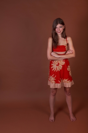 Young woman on a brown background with arms folded in typical spokesperson pose with room for copy photo