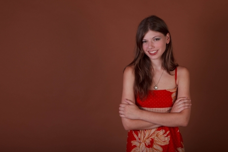 spokesperson: Young woman on a brown background with arms folded in typical spokesperson pose with room for copy Stock Photo