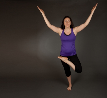 Studio shot of a fit brunette woman doing yoga stretching and flexibility exercises on a grey background photo